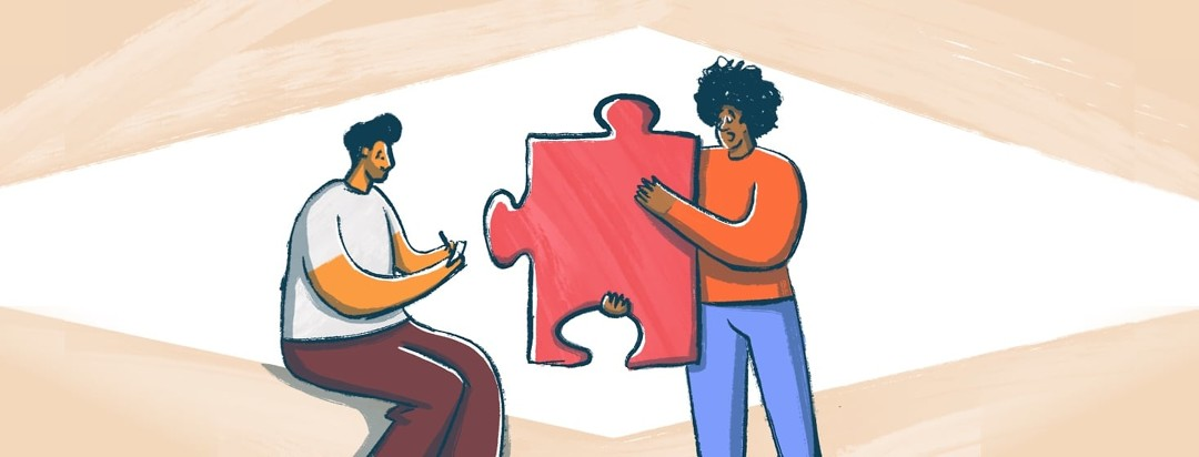 Two men talking to each other. One is standing and holding a red puzzle piece. The second man is sitting and taking notes.