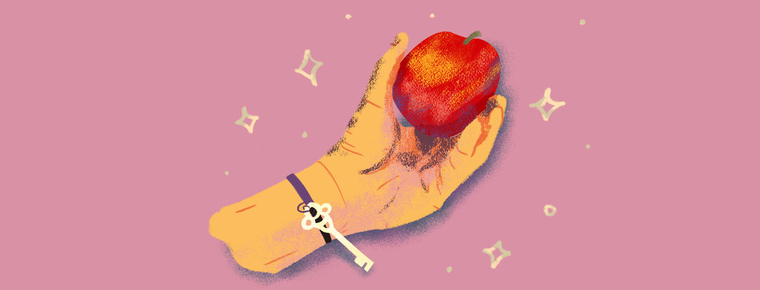 Hand with a key bracelet holding a healthy looking apple