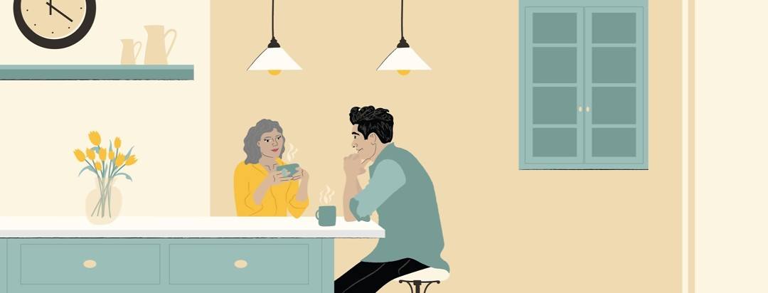 a man and a woman sitting together at a kitchen counter