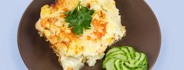 Cauliflower Cup on a brown plate with cucumber garnish off to the side.
