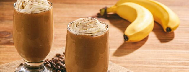 Coffee oat smoothie surrounded by coffee beans and a banana