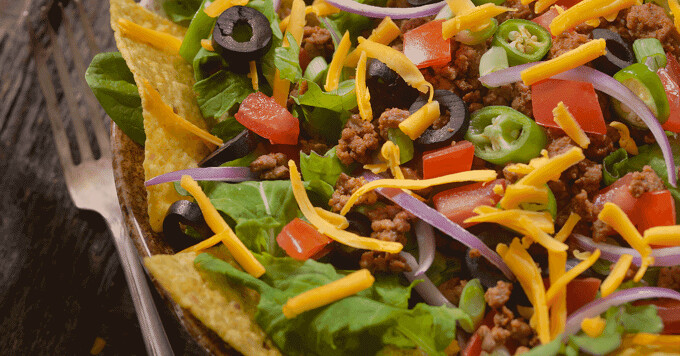 taco salad in a tortilla bowl with a fork on the side.