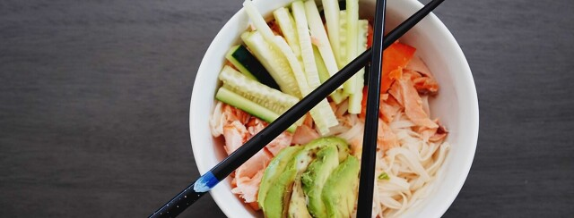 Noodle Salmon Bowl with chopsticks laid across the top of the white bowl.