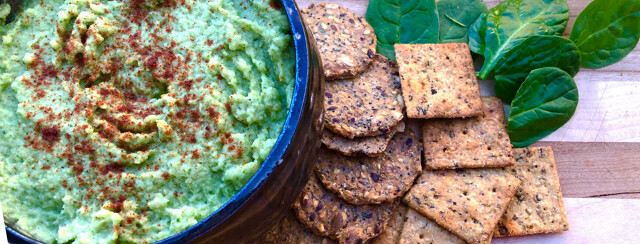 Spinach artichoke dip on a plate with a variety of crackers