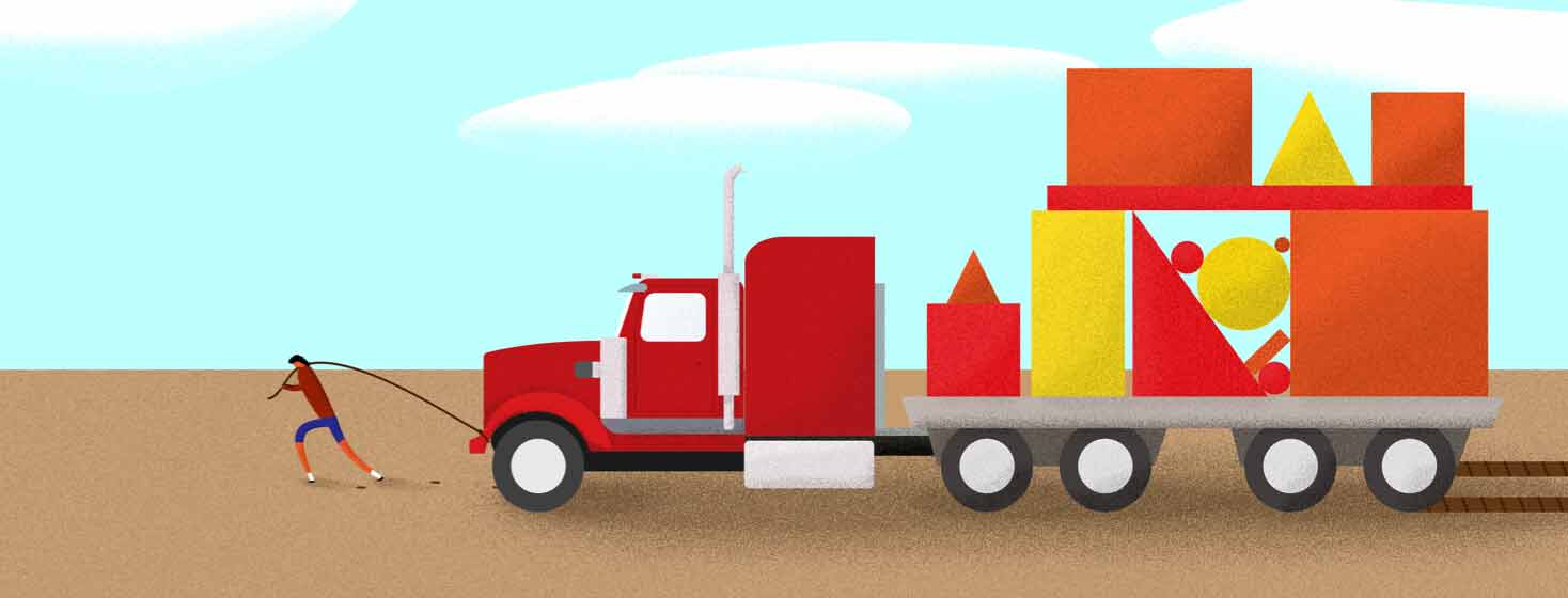 A person pulling a giant 18 wheeler stacked with pieces, building blocks, through the mud. Adult, burden, struggle, truck.