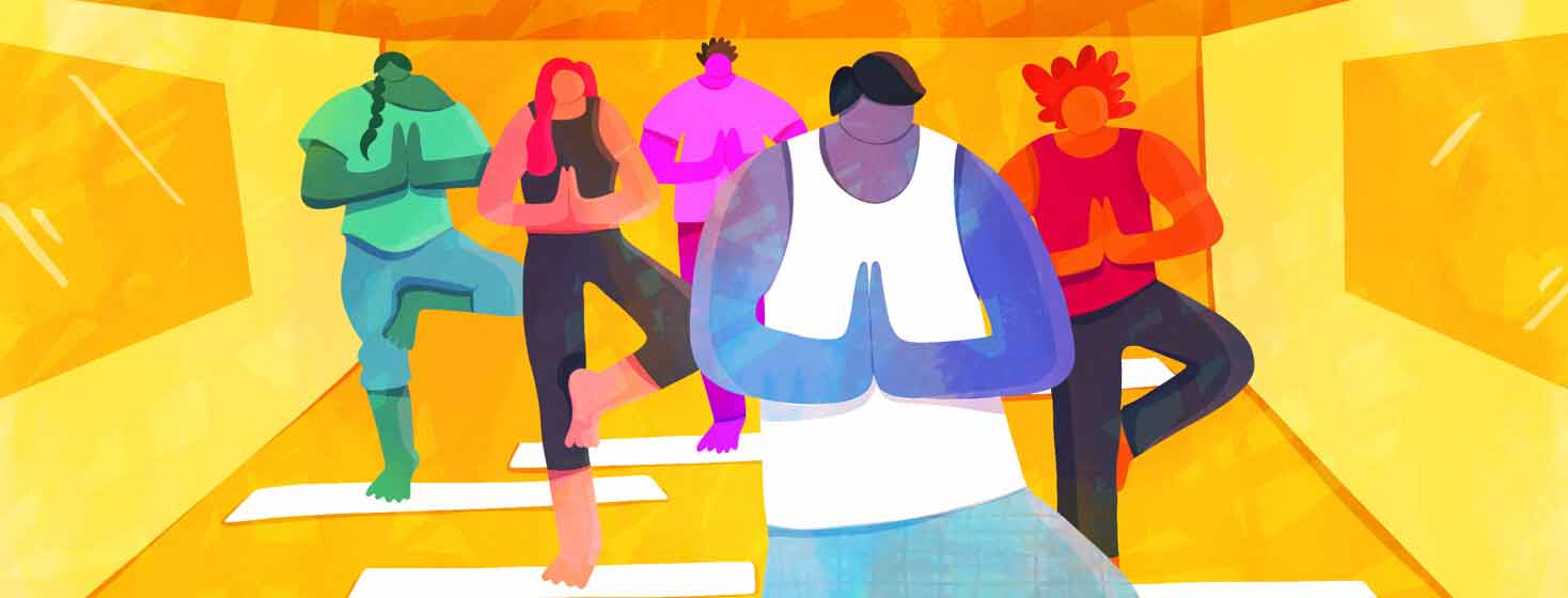 A man leading a group of people in a yoga studio. Exercise, meditation, group workout, stretch